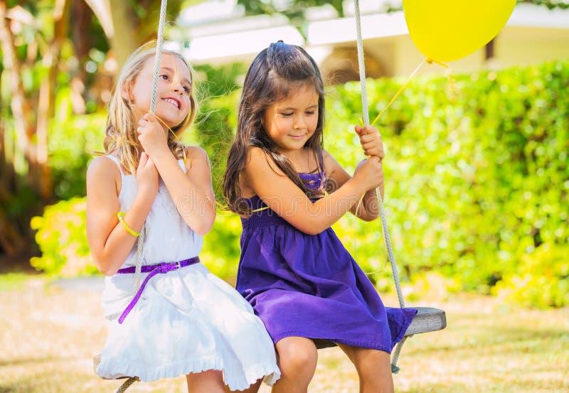 Meisjes die op Schommeling spelen royalty-vrije stock afbeelding