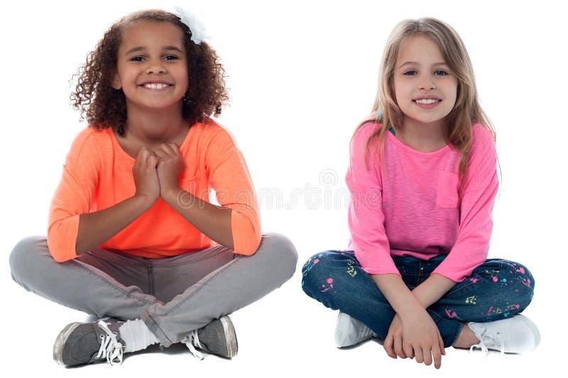 Meisjes die op vloer zitten stock afbeeldingen