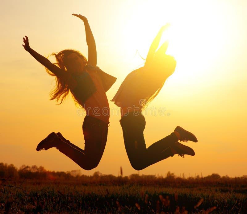 Meisjes die over zonsondergang springen stock foto's