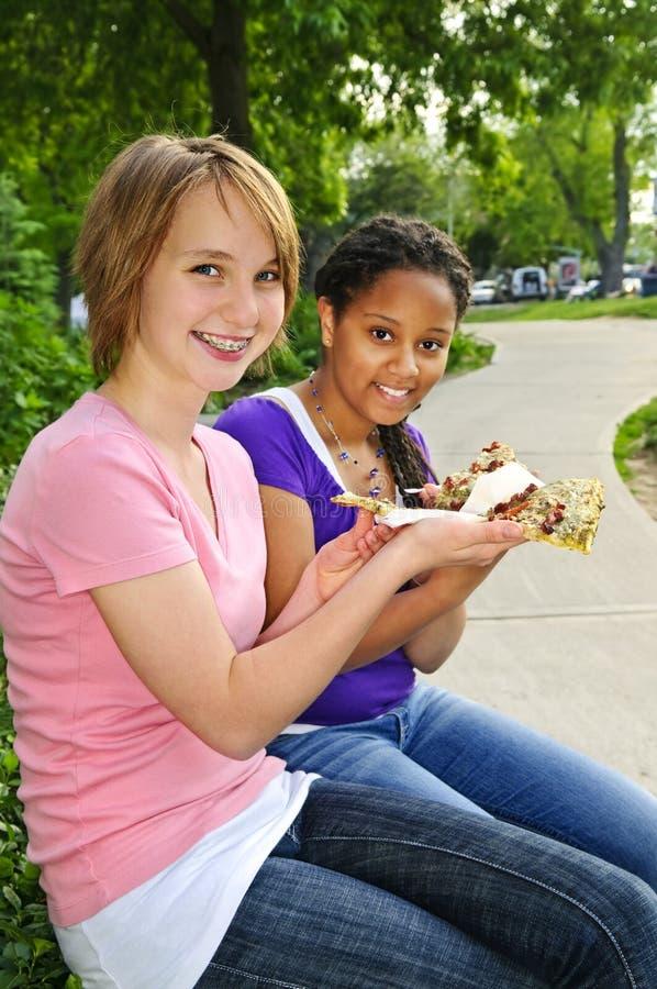 Meisjes die pizza eten stock foto