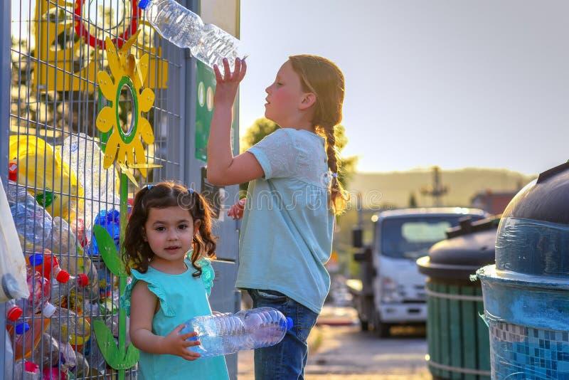 Meisjes die Plastic Waterflessen recycleren Krat van plastic waterflessen klaar voor recycling in bak stock foto
