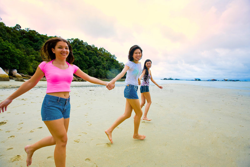 Meisjes die pret hebben bij het strand stock afbeeldingen