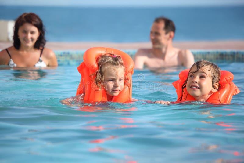 Meisjes die in reddingsvesten met ouders in pool baden stock fotografie