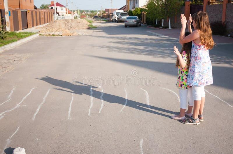 Meisjes die samen buiten thuis op een de zomerdag spelen stock foto's