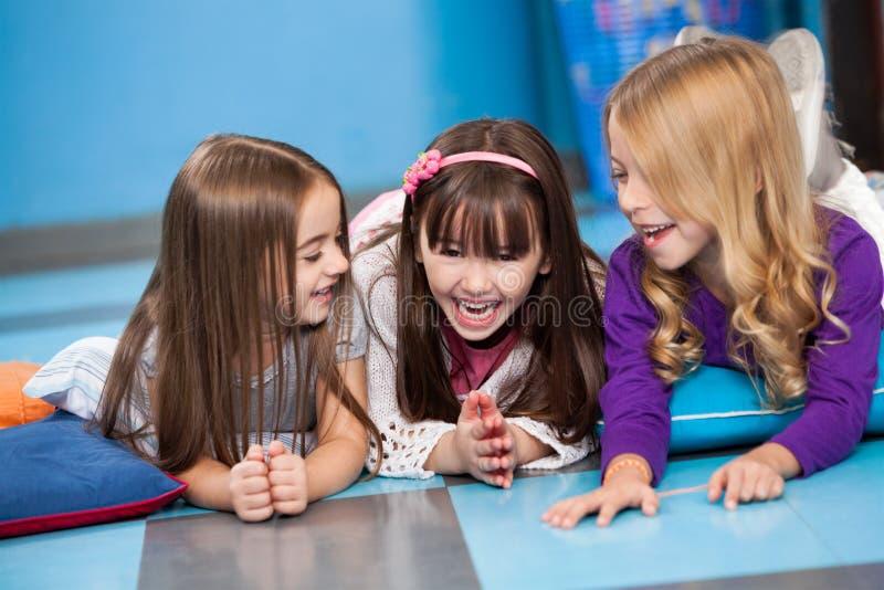 Meisjes die terwijl het Liggen op Vloer lachen stock fotografie