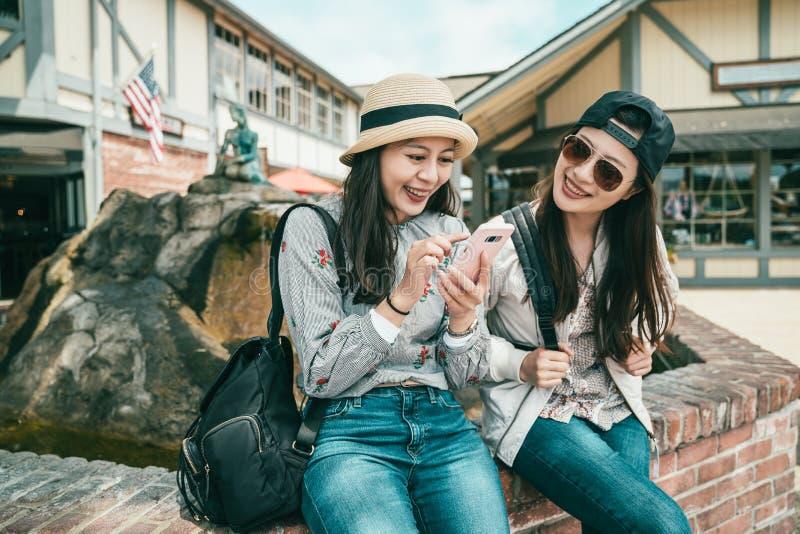 Meisjes die terwijl het zitten aan de fontein lachen royalty-vrije stock afbeeldingen