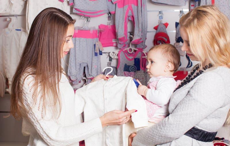 Meisjes die uit voor kleren winkelen stock afbeeldingen