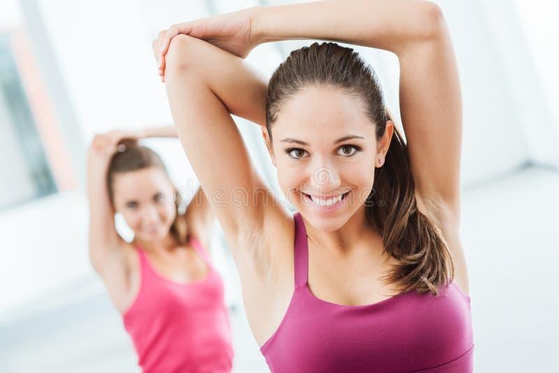 Meisjes die uitrekkende oefeningen doen bij de gymnastiek royalty-vrije stock afbeelding