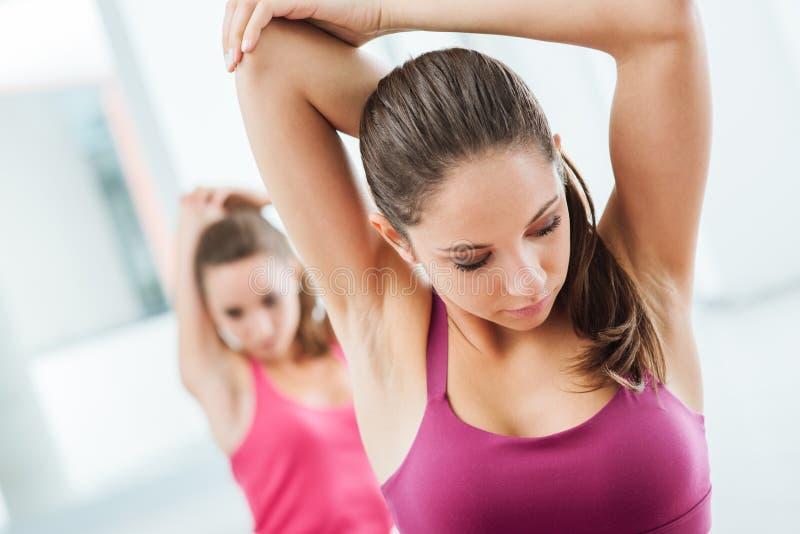 Meisjes die uitrekkende oefeningen doen bij de gymnastiek stock fotografie