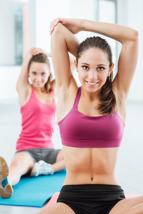 Meisjes die uitrekkende oefeningen doen bij de gymnastiek stock afbeeldingen