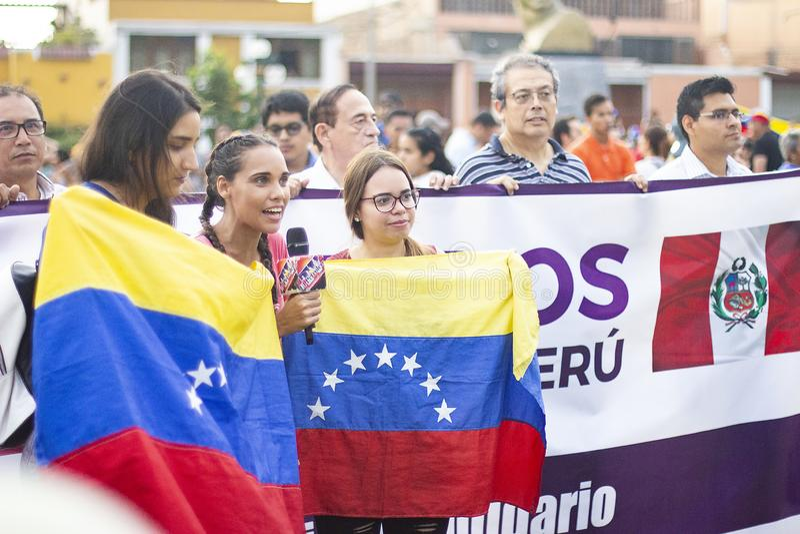 Meisjes die Venezolaanse vlag met Peruviaanse vlag houden stock afbeeldingen