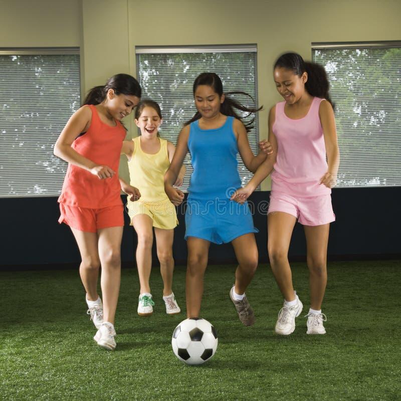 Meisjes die voetbal spelen.