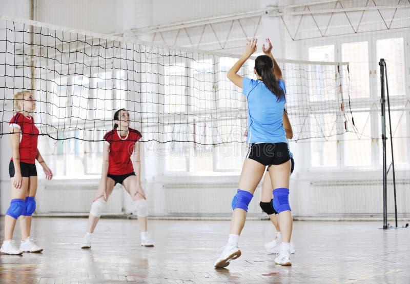 Meisjes die volleyball binnenspel spelen stock afbeeldingen