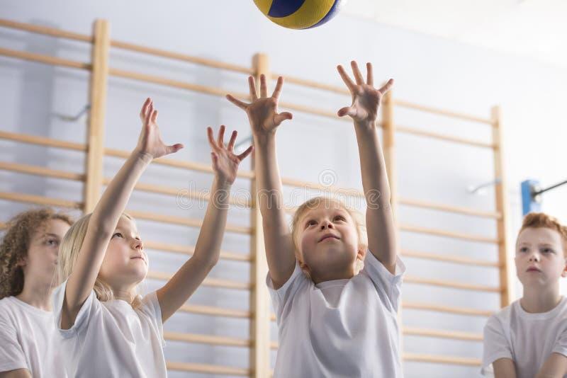 Meisjes die volleyball tijdens een spel met haar partners van het schoolteam springen te raken stock fotografie