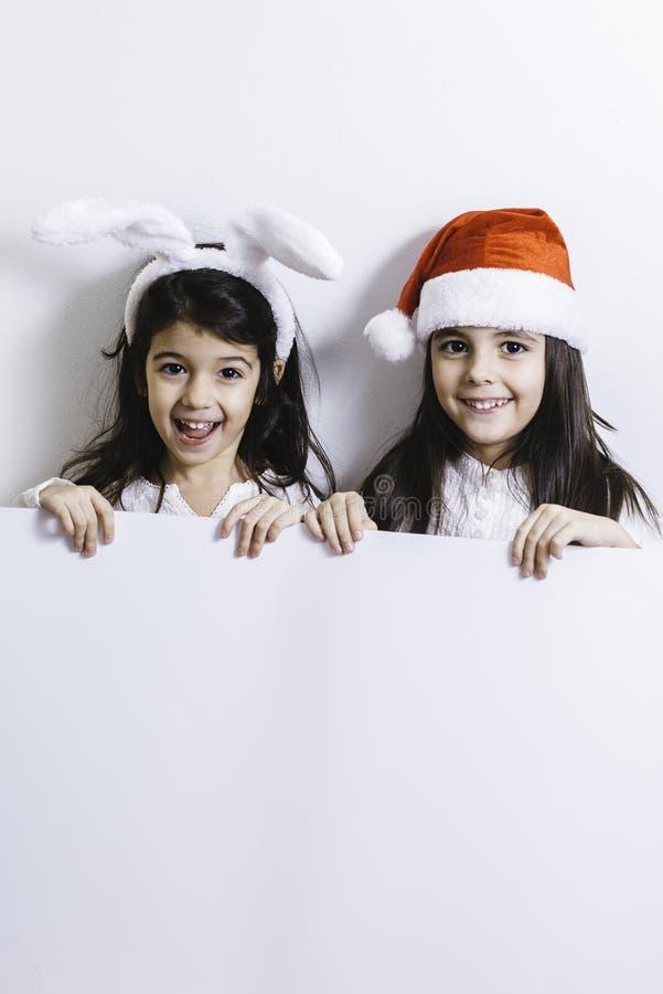 Meisjes die voor Kerstmis en Nieuwjaarvakantie stellen stock afbeelding