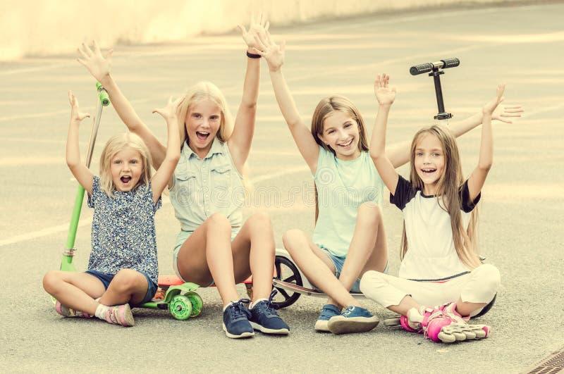 Meisjes die zitting op de grond met opgeheven handen glimlachen royalty-vrije stock foto