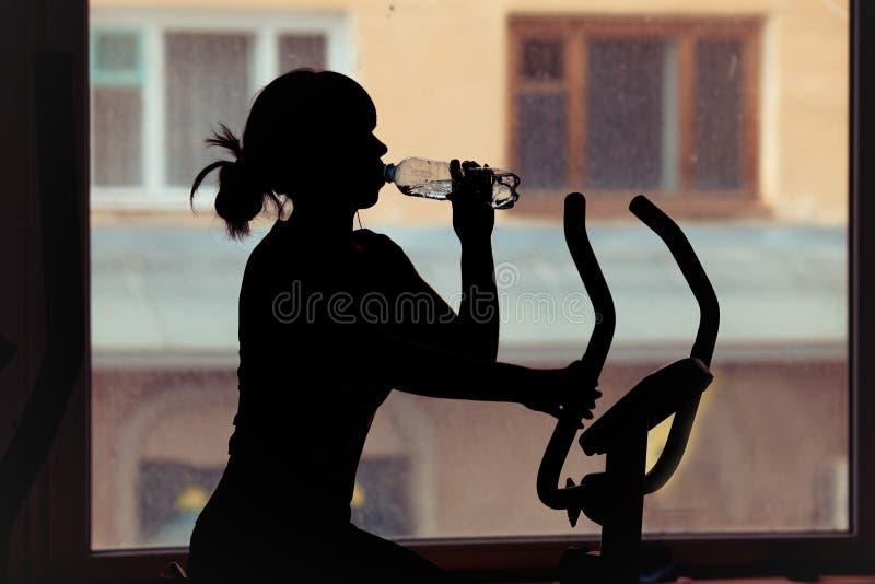Meisjes drinkwater in een gymnastiek Silhouet stock foto's