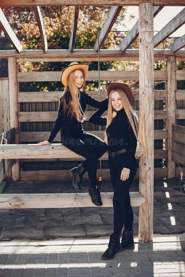 Meisjes in een cowboyshoed op een boerderij stock afbeelding