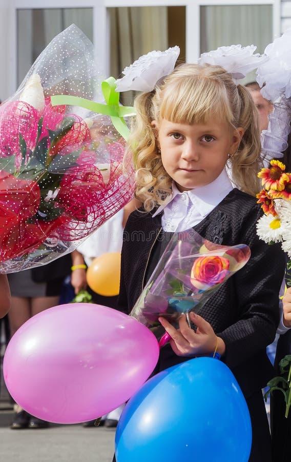 Meisjes eerste nivelleermachine op de school op 1 September opstelling stock afbeelding