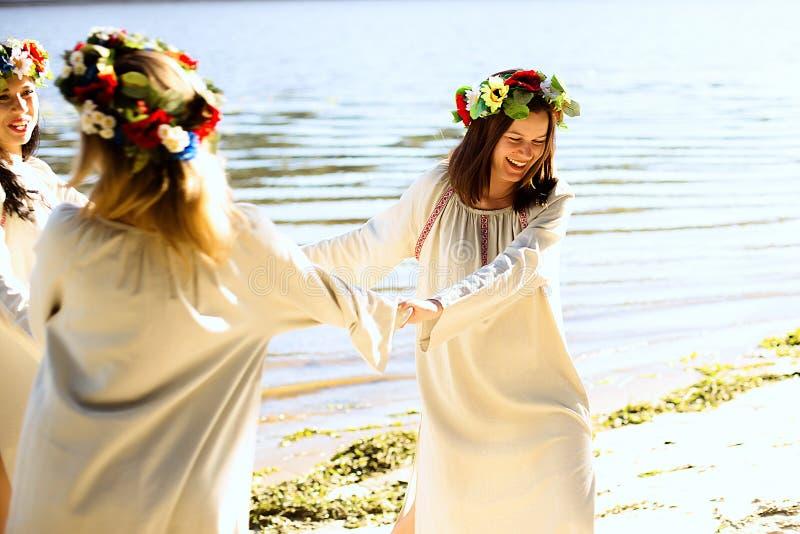 Meisjes in etnische kleren met kroon van bloemen het vieren stock fotografie