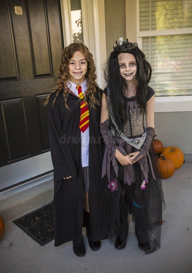 Meisjes gaande truc of het behandelen op Halloween in hun kostuum stock afbeelding