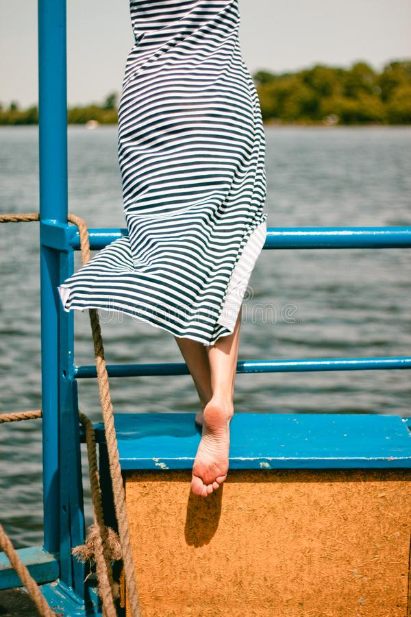 Meisjes gestreepte kleding die zich oud schip bevinden die kust kijken royalty-vrije stock afbeeldingen