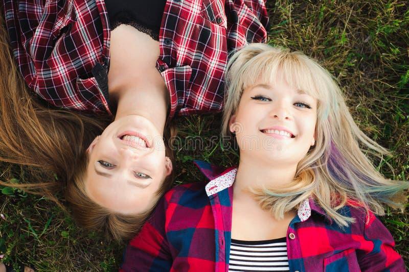 Meisjes het liggen hoofd - - hoofd op een gras royalty-vrije stock foto's