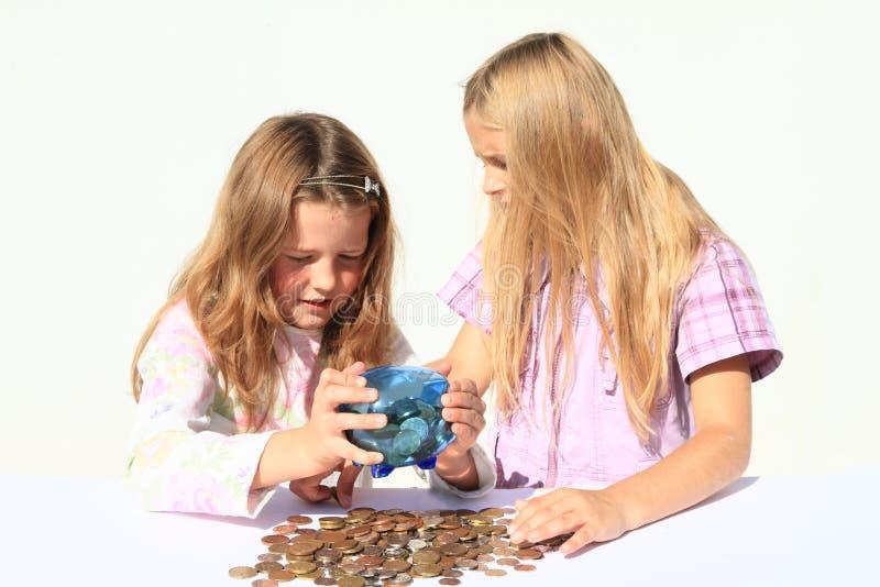 Meisjes - jonge geitjes die geld van besparingsvarken weggaan stock fotografie