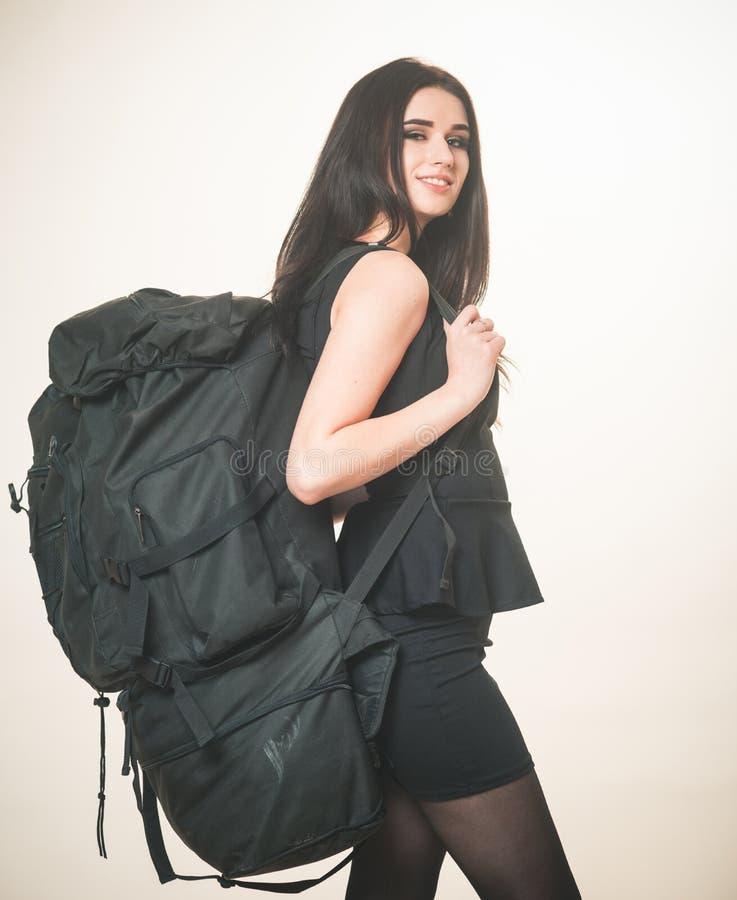Meisjes klassieke zwarte kleding en toeristisch rugzakmateriaal Bedrijfsdame die met rugzak reizen De vrouw draagt bagage stock afbeelding