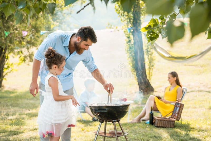 Meisjes lettende op vader die vlees bij de barbecuegrill voorbereiden tijdens familiepicknick stock foto