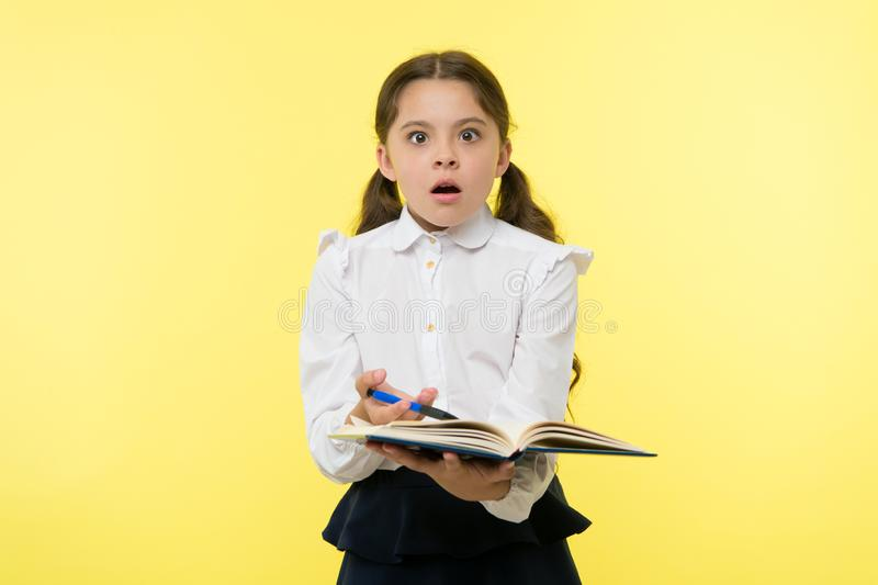 Meisjes leuk schoolmeisje in eenvormig greepboek met informatie gele achtergrond De leerling krijgt informatie van boek Kind royalty-vrije stock afbeeldingen
