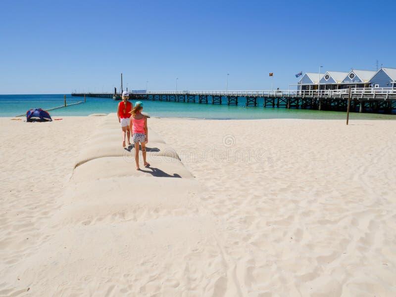 Meisjes met heldere klerengang op het strand stock afbeelding
