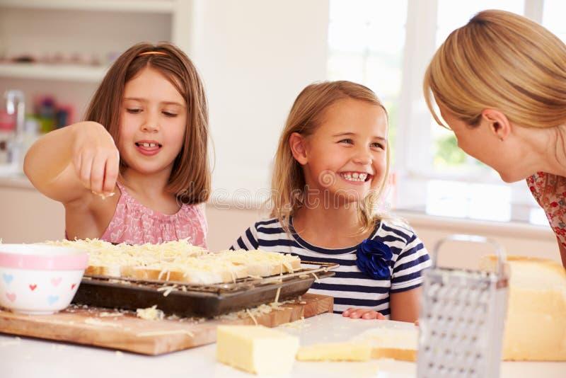 Meisjes met Moeder die Kaas op Toost maken stock afbeelding