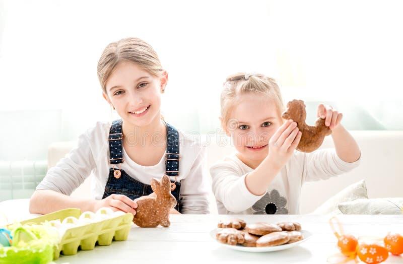 Meisjes met Pasen-gemberkoekjes in verschillende vormen stock foto's