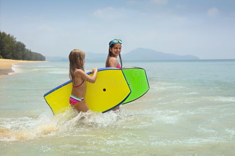 Meisjes met surfende raad die op tropisch oceaanstrand spelen De pret van het de zomerwater voor surferjonge geitjes stock foto