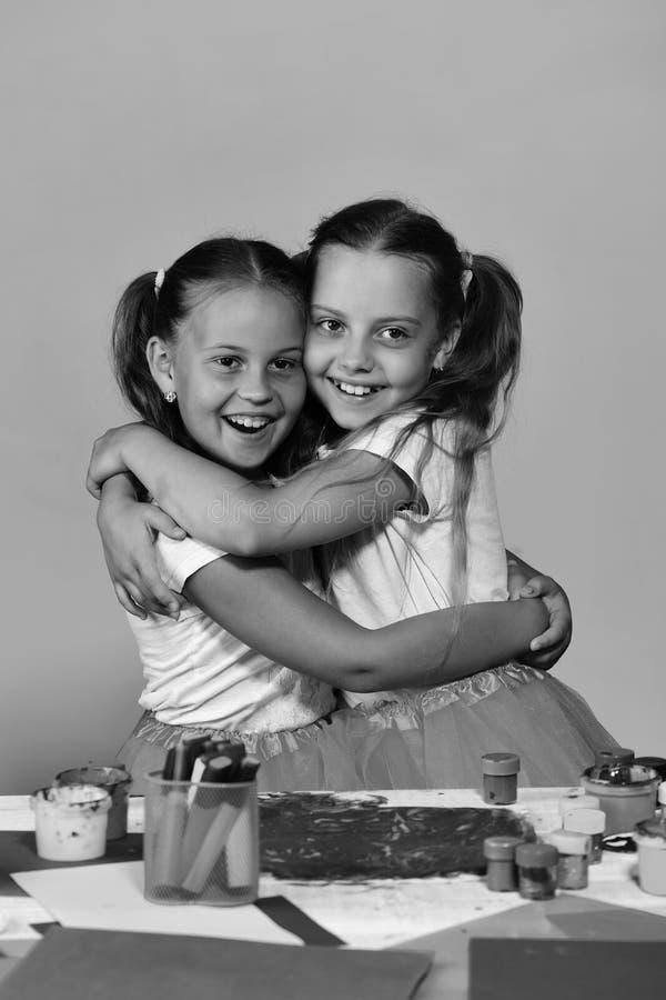 Meisjes met vrolijke gezichten door hun kunstbureau Kunstenaars met paardestaartenomhelzing elkaar Creativiteit en verbeeldingsco royalty-vrije stock foto's