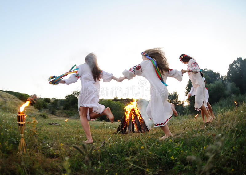 Meisjes in Oekraïense nationale overhemden die rond een kampvuur dansen Midsumer royalty-vrije stock foto's