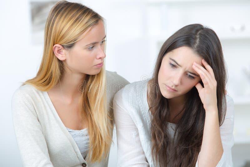 Meisjes ondersteunende gedeprimeerde vrouwelijke vriend binnen stock afbeelding