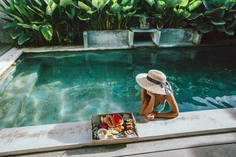 Meisjes ontspannen en fruit eten in het zwembad op luxe villa op Bali royalty-vrije stock afbeeldingen