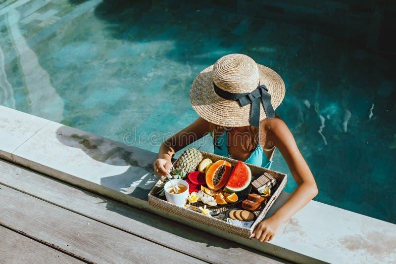 Meisjes ontspannen en fruit eten in het zwembad op luxe villa op Bali stock foto's