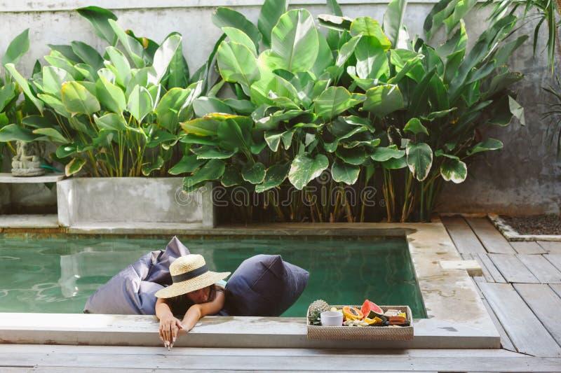 Meisjes ontspannen en fruit eten in het zwembad op luxe villa op Bali royalty-vrije stock fotografie