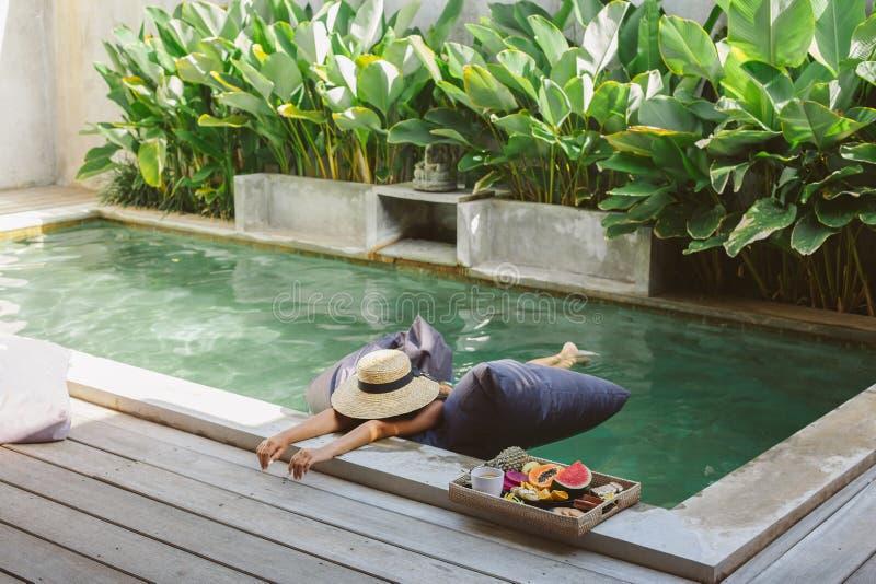 Meisjes ontspannen en fruit eten in het zwembad op luxe villa op Bali royalty-vrije stock foto's