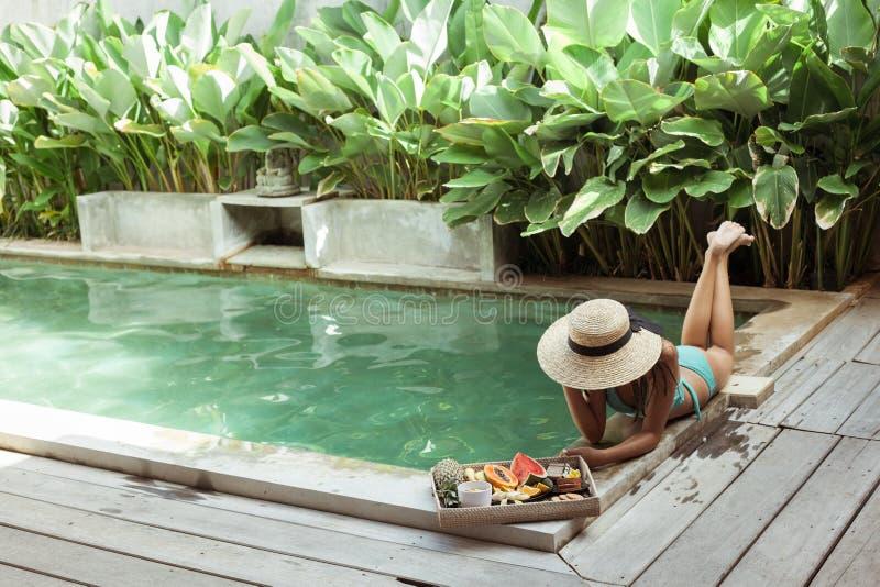 Meisjes ontspannen en fruit eten in het zwembad op luxe villa op Bali royalty-vrije stock afbeelding