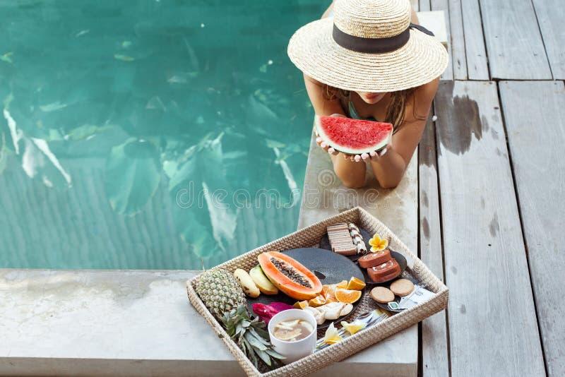 Meisjes ontspannen en fruit eten in het zwembad op luxe villa op Bali stock afbeelding