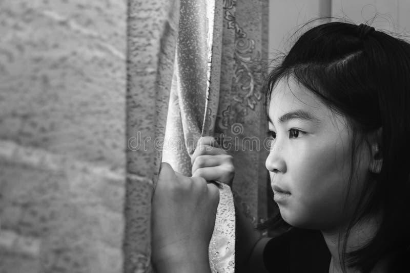 Meisjes open gordijn die buiten met gelet op afwezig kijken royalty-vrije stock foto's