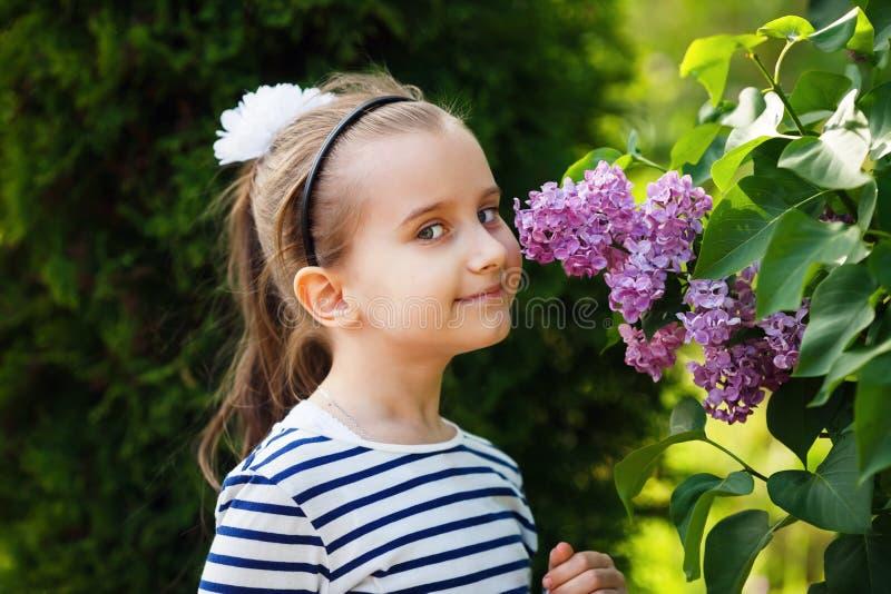 Meisjes ruikende Seringen stock afbeeldingen