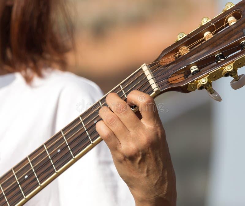 Meisjes` s hand het spelen gitaar stock afbeelding