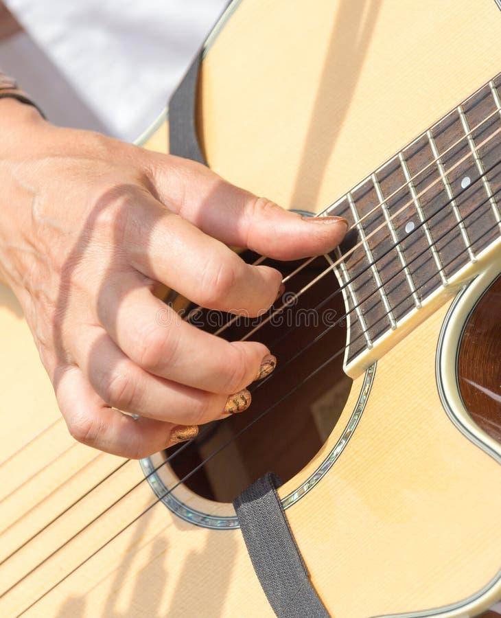 Meisjes` s hand het spelen gitaar stock fotografie