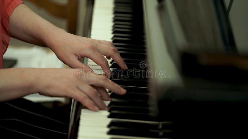 Meisjes` s handen op het toetsenbord van de piano Het meisje speelt piano, sluit omhoog piano Handen op de witte sleutels van de  royalty-vrije stock foto