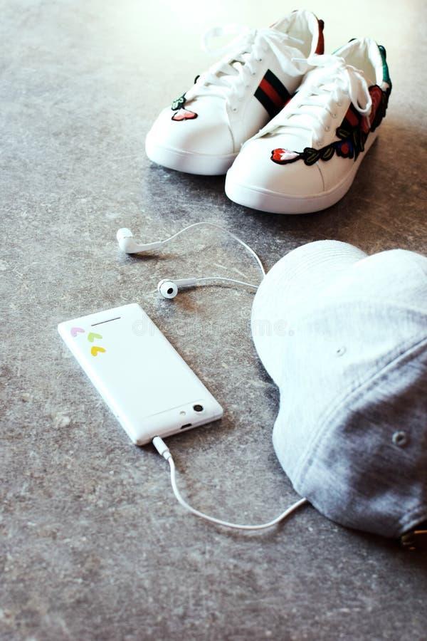 Meisjes` s toebehoren - witte smartphone, oortelefoons, tennisschoenen en grijs GLB stock foto's